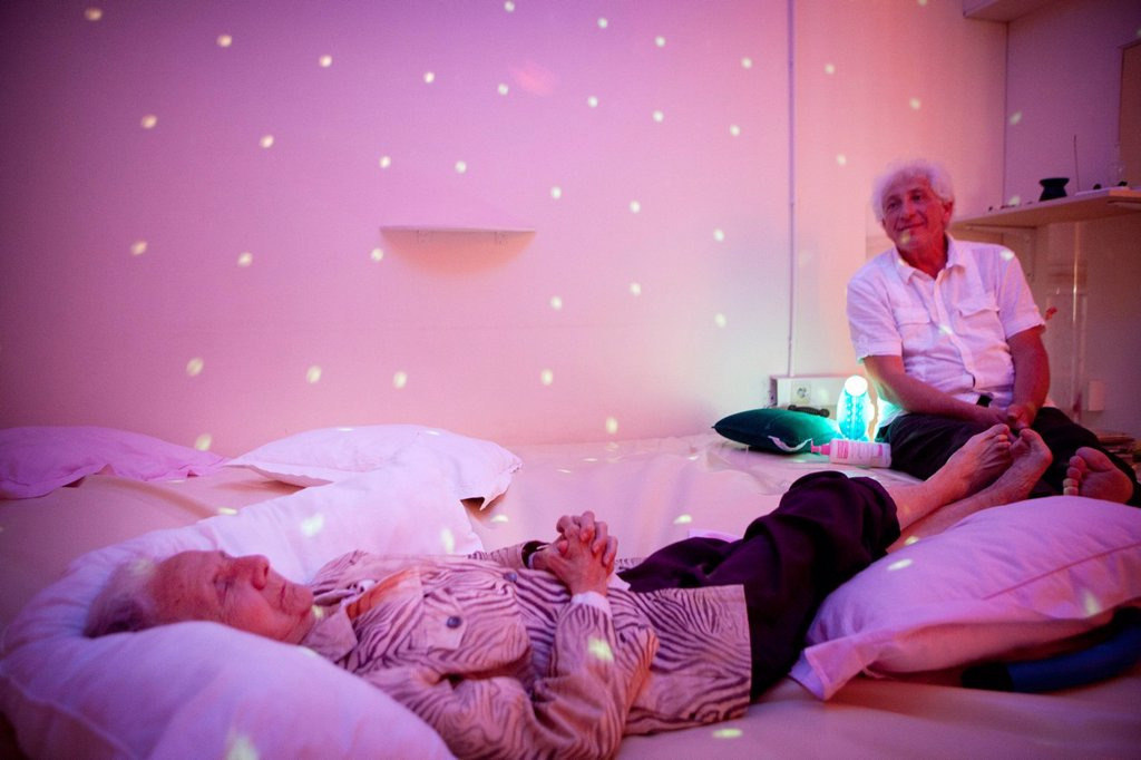 Stock Photo: 824-13434 SNOEZELEN & ALZHEIMER. Reportage in a snoezelen room in Liège. Mony, 85, who has Alzheimer´s disease, moves around in this multi_sensory environment, which is both soothing and stimulating, with Marc Thiry, a physiotherapist specialising in psychomotor education. Professor Thiry has been following Mony since her disease was diagnosed 5 years ago. By stimulating the senses, these rooms allow people with Alzheimer´s, who, despite their disease, maintain a sensorial memory, to lower their anxiety l