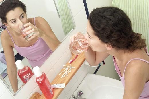 Stock Photo: 824-14156 DENTAL HYGIENE,  WOMAN. DENTAL HYGIENE,  WOMAN Model. Plaque-fighting mouthwash.