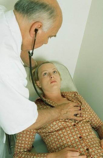 SYMPTOMATOLOGY, WOMAN. SYMPTOMATOLOGY  WOMAN Reconstructed scene. Doctor auscultating patient with stethoscope. : Stock Photo