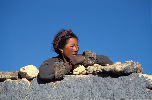 Stock Photo: 824-21798 ASIAN WOMAN. ASIAN WOMAN Winter trekking at the village Tingri near the southern frontier of Tibet and the norther frontier of Nepal at the monastery Rongbuk at the foot of the northern face and the camp at the basis of the Everest Chomolungma in Tibetan. Village and inhabitants from the Zemukh track leading to the Everest.