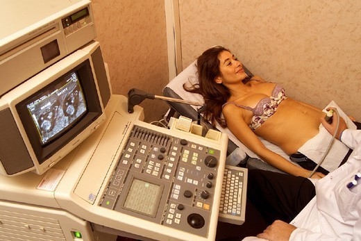 PREGNANT WOMAN, ULTRASONOGRAPHY. PREGNANT WOMAN, ULTRASONOGRAPHY Photo essay. Arm and fingers displayed on screen. : Stock Photo