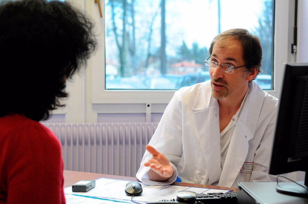 TRANSSEXUAL IN CONSULTATION. Photo essay at Henry Gabrielle hospital in Lyon, France. Urology consultation with Dr Nicolas Morel_Journel, surgeon_urologist. First consultation of a trans woman patient for a sex reassignment surgery, vaginoplasty. : Stock Photo