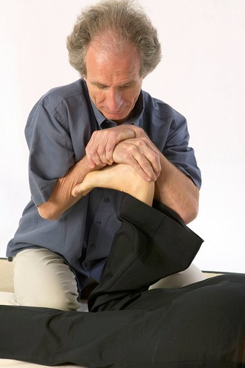 SHIATSU. SHIATSU Photo essay on a Shiatsu session. The practice of Shiatsu, Japanese discipline being exercised on the ground, it consists in stimulating the body with rhythmic pressures at the level of the meridians of acupuncture. Here, stretching of the Achille´s tendon. : Stock Photo
