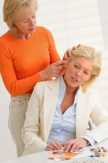 Stock Photo: 824-29623 WOMAN CONSULTING FOR HEARING PB. WOMAN CONSULTING FOR HEARING PB. Models. Hearing aids.