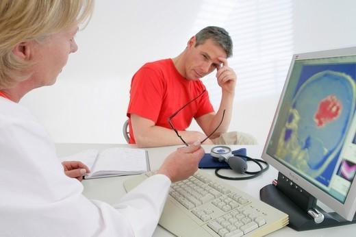 MAN IN CONSULTATION. MAN IN CONSULTATION Models. On screen, MRI of a brain tumor. : Stock Photo