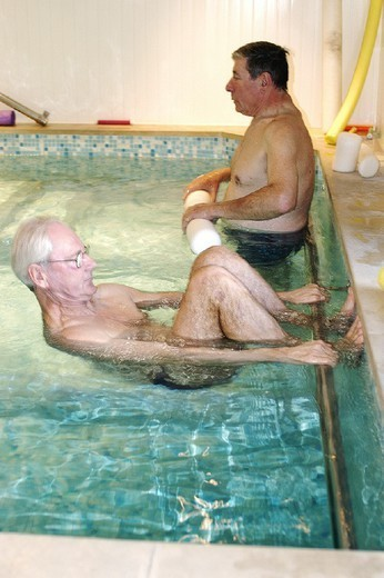 Stock Photo: 824-45877 REHABILITATION, ELDERLY PERSON. REHABILITATION, ELDERLY PERSON Photo essay. Therapy pool at Dinan, in the Britanny region of France.   The sensation of weightlessness is the large advantage to re-education in a pool, thus facilitating the movement by alleviating stress to joints. Warm water (34°C) relaxes the muscles, the patient regains confidence by rediscovering ease of movement, and this flexibility is gradually integrated into daily activities. Pool re-education is principally indicat
