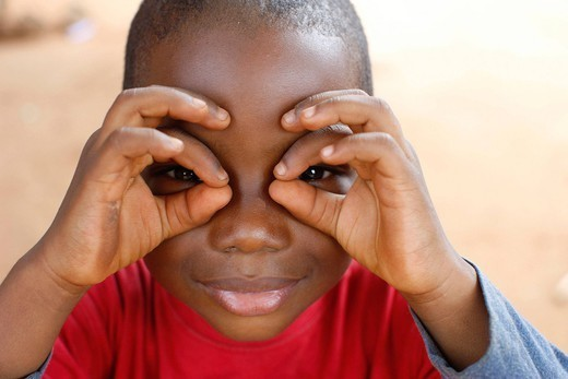 AN AFRICAN CHILD. Young boy playing with his fingers. : Stock Photo