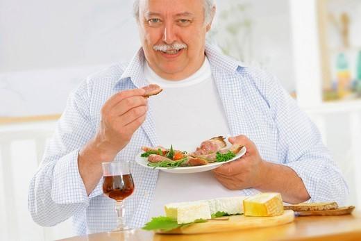 ELDERLY PERSON EATING PORK MEAT. Model. : Stock Photo