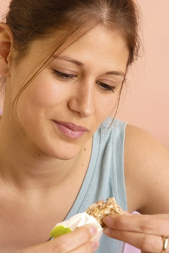 Stock Photo: 824-51286 WOMAN SNACKING. WOMAN SNACKING Model.