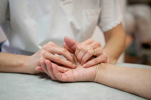 Stock Photo: 824-53553 REHABILITATION, ELDERLY PERSON. Photo essay from La Croix Saint_Simon Hospital, Paris, France. Session of physical therapy following a fracture and a tear of the thumb ligaments.