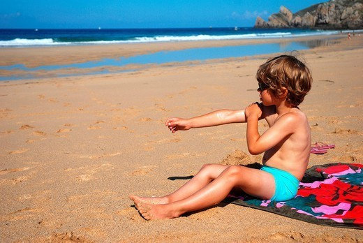 SHIELDING FROM SUNBURN. 7_year_olf boy putting on sun screen on the beach to protect himself from sun burns. : Stock Photo