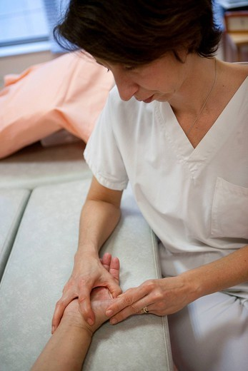 Stock Photo: 824-54107 REHABILITATION, ELDERLY PERSON. Photo essay from La Croix Saint_Simon Hospital, Paris, France. Session of physical therapy following a fracture and a tear of the thumb ligaments.