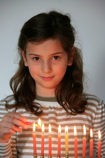 CHILD INDOORS. CHILD INDOORS Light_up of the candles for Hanouka. : Stock Photo