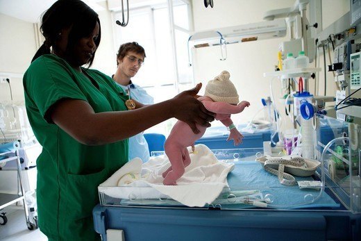 Stock Photo: 824-58452 NEWBORN REFLEX. Photo essay at the maternity of the Diaconesses hospital in the 12th district of Paris, France. Newborn baby boy of 2 hours. The child care aid doing the stepping reflex in presence of the father.