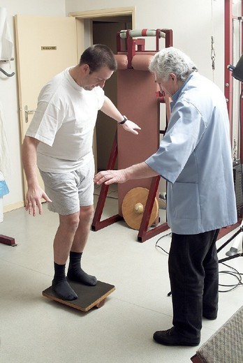 MAN IN PHYSICAL THERAPY. MAN IN PHYSICAL THERAPY Patient and health professional. A wobble board is used for developing proprioception (balance) following a sprain to the lateral inner ligament. : Stock Photo
