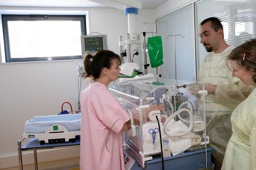 Stock Photo: 824-68412 NEONATOLOGY. NEONATOLOGY Photo essay at the hospital of Meaux 77, France. Department of neonatal resuscitation. The parents in yellow smock at the bedside of their premature twins with a pediatric nurse.