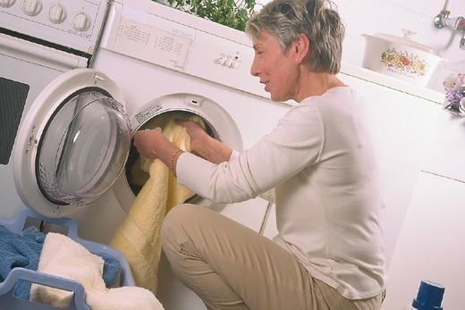 INTERIOR, WOMAN DOING LAUNDRY. INTERIOR, WOMAN DOING LAUNDRY Model. : Stock Photo