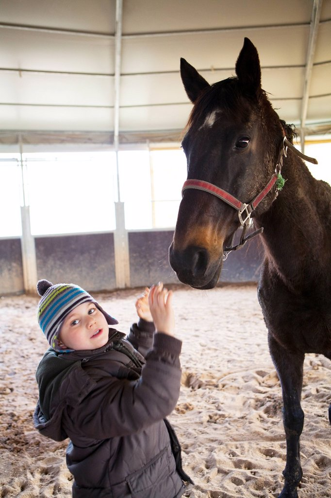 HIPPOTHERAPY. Photo essay at EQUISENS, a therapeutic riding centre in Asniere_les_Dijon France. Hippotherapy session with a child having autistic disorders. : Stock Photo