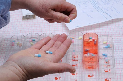 Stock Photo: 824-72523 MEDICATION DISTRIBUTION. Independent nurse, in Vénissieux, France. Independent nurse at the home of a diabetic patient of type 1. The nurse prepare the pill box of the patient , we can see a prescription for long_term care.
