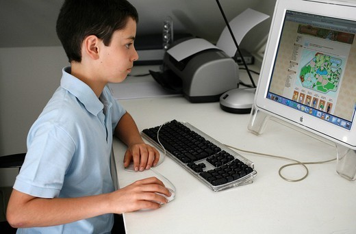 CHILD, COMPUTER. CHILD COMPUTER Schoolboy using an educational game on the computer. : Stock Photo