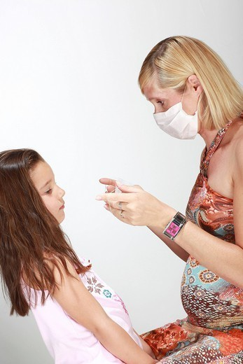 PREVENTION, MASK. Models. Woman 5 months pregnant and her 6_year_old daughter. : Stock Photo