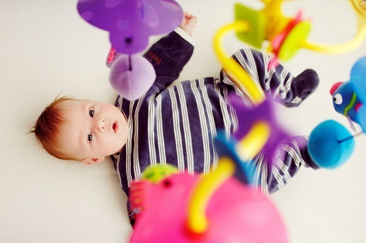 INFANT PLAYING INDOORS. INFANT PLAYING INDOORS Model. Playful stimulation of a baby using a mobile : Stock Photo