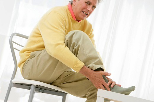 ANKLE PAIN ELDERLY PERSON. Model. : Stock Photo