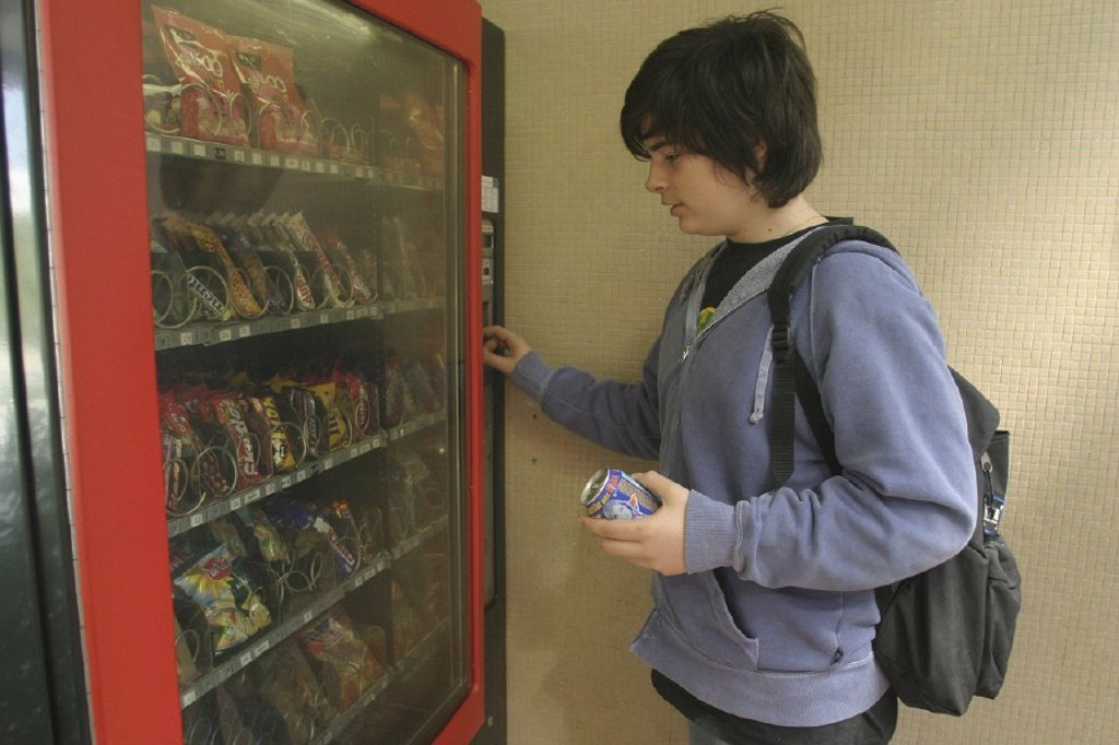 ADOLESCENT SNACKING. ADOLESCENT SNACKING Model. Candy vending machine. : Stock Photo