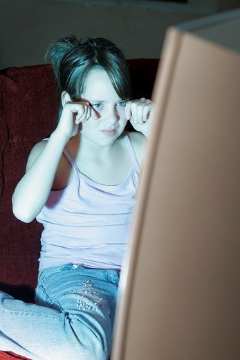 Stock Photo: 824-83011 CHILD WATCHING TELEVISION. CHILD WATCHING TELEVISION Model. 11_year_old girl.