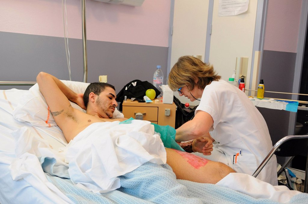 NURSE DISPENSING CARE. Photo essay at Henry Gabrielle hospital in Lyon, France. Department of urology. Postoperative nursing care of trans man patient after a sex reassignment surgery, phalloplasty. Disinfection of the forearm which provided the skin for the phalloplasty. : Stock Photo