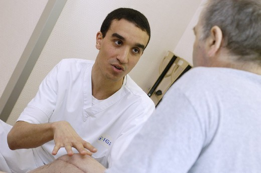 MAN IN REHABILITATION. MAN IN REHABILITATION Photo essay from hospital. Institut Gustave-Roussy, in the French region of Ile-de-France. Anti-cancer center. Physical therapist massages a patient who received a prosthesis following an operation to remove the tumor. : Stock Photo