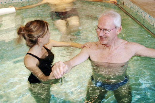 Stock Photo: 824-94756 REHABILITATION, ELDERLY PERSON. REHABILITATION, ELDERLY PERSON Photo essay. Therapy pool at Dinan, in the Britanny region of France.   The sensation of weightlessness is the large advantage to re-education in a pool, thus facilitating the movement by alleviating stress to joints. Warm water (34°C) relaxes the muscles, the patient regains confidence by rediscovering ease of movement, and this flexibility is gradually integrated into daily activities. Pool re-education is principally indicat