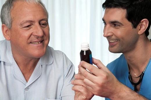 ELDERLY PERSON TAKING MEDICATION. Models. : Stock Photo