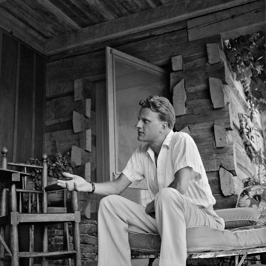 USA, North Carolina, Montreat, Billy Graham makes a point during an interview at his home, September 1958 : Stock Photo