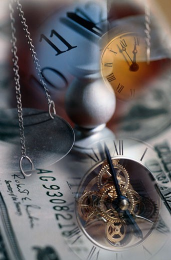 Clocks and balance pan superimposed on US dollar bills : Stock Photo