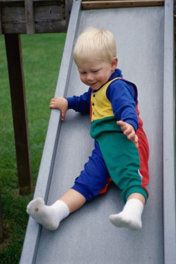 Baby boy coming down a slide in a park : Stock Photo