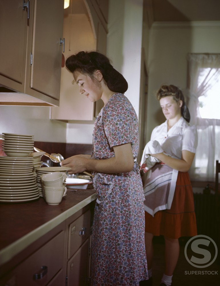 Stock Photo: 911-3078 Side profile of a mother working in the kitchen with her daughter