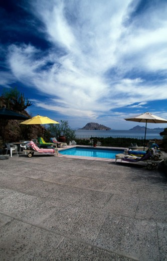 Lounge chairs at the poolside in a tourist resort, Danzante Eco Resort, Sea of Cortez, Mexico : Stock Photo