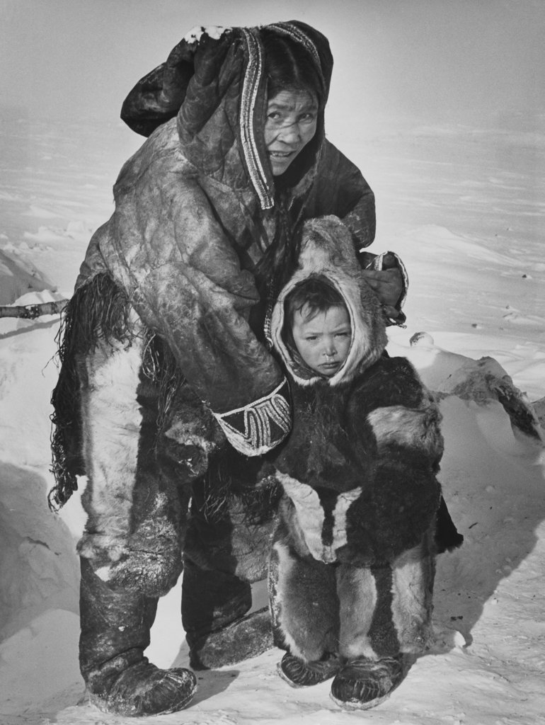 Mid adult Eskimo woman with her son standing on a polar landscape, Northwest Territories, Canada : Stock Photo