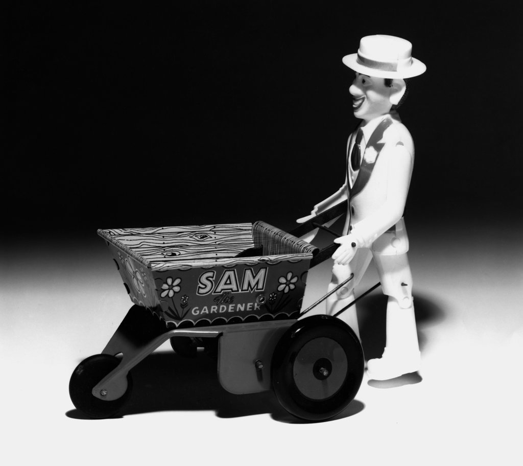 Stock Photo: 990-2601 Side profile of a male figurine pushing a wheelbarrow, Sam the City Gardner, 1940
