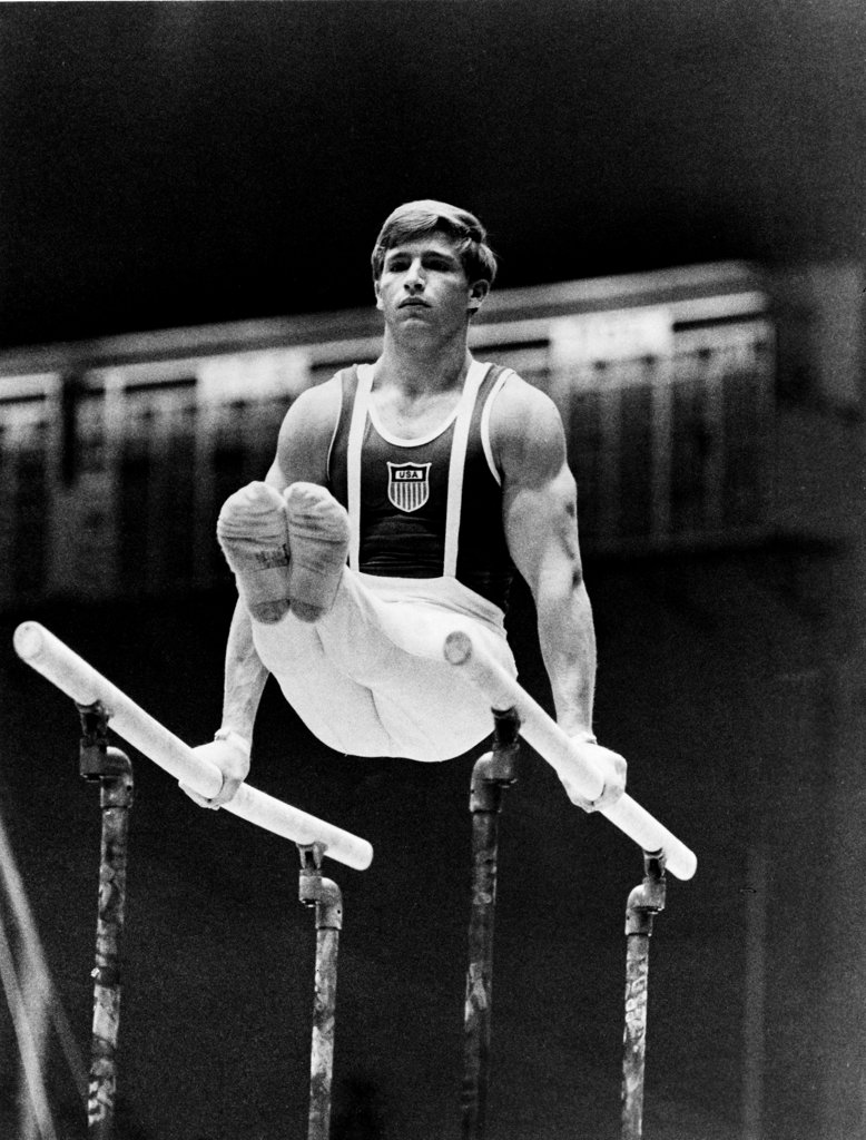 Stock Photo: 990-3047 Young man performing on parallel bars at the Olympic games