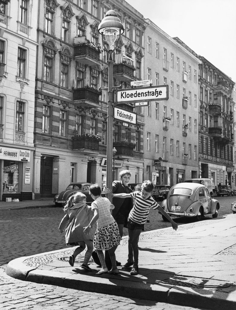 Boys and girls playing around a lamppost, Kreuzberg, Berlin, Germany : Stock Photo