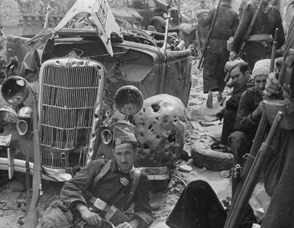 Group of soldiers near a damaged car during a war, Spanish Civil War : Stock Photo
