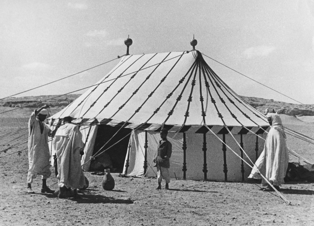 Stock Photo: 990-359091 Men building tent on desert, boy watching them
