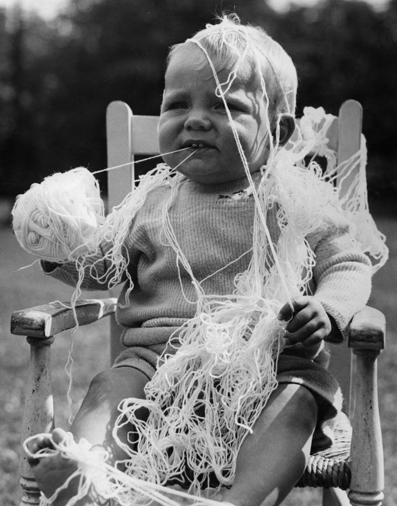 Stock Photo: 990-359102 Baby boy covering by wool and holding ball of wool