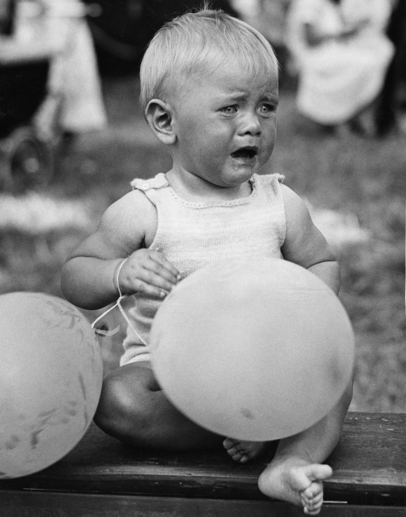 Stock Photo: 990-359106 Crying baby girl with balloons