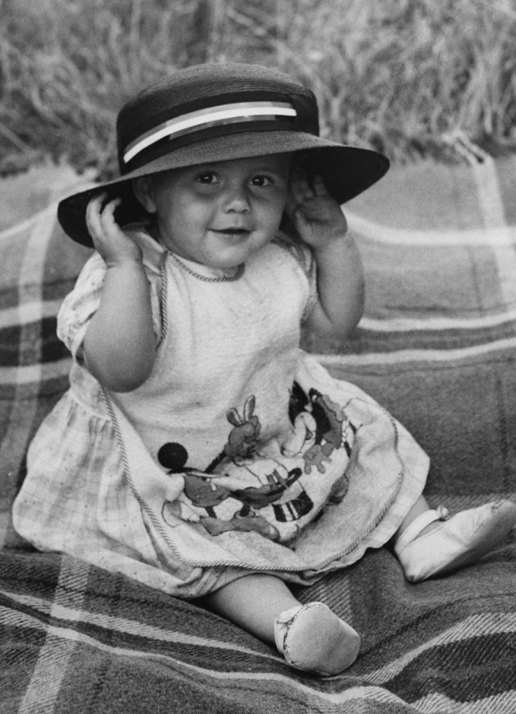 Baby girl sitting on blanket, smiling and wearing hat : Stock Photo