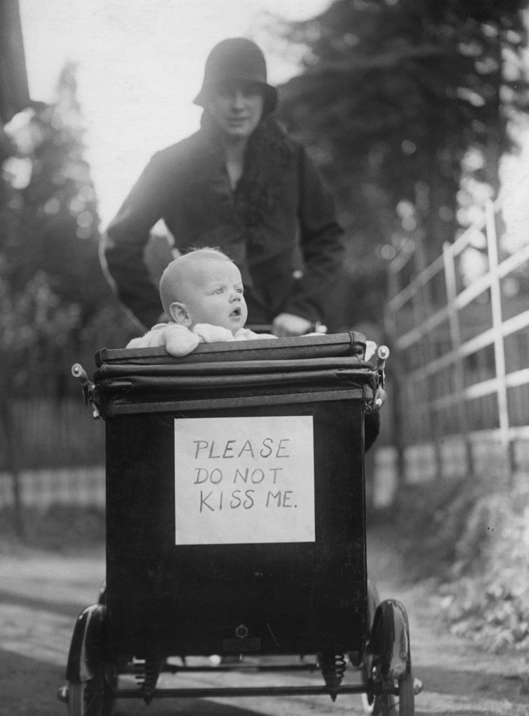 Mother with baby in baby stroller with 'please do not kiss me' placard : Stock Photo