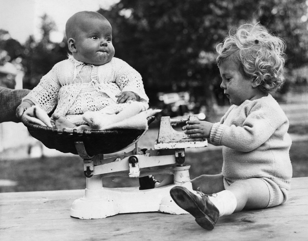 Baby girl sitting on scale's bowl and older brother weighting her : Stock Photo