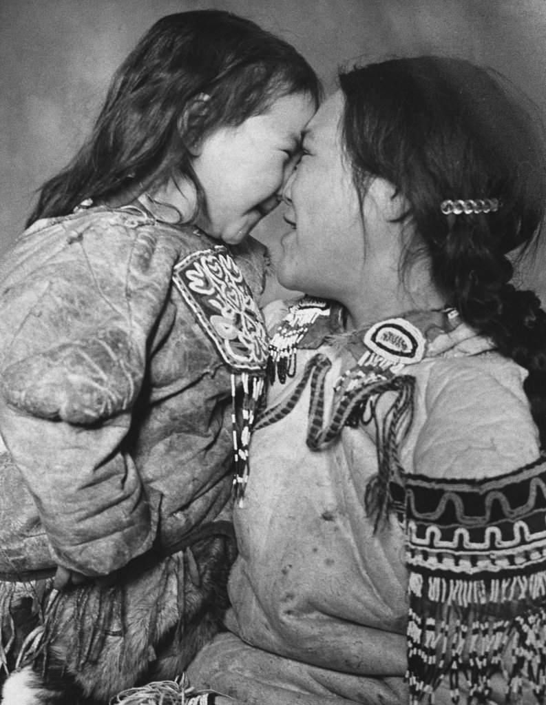 Mid adult Eskimo woman and her daughter rubbing noses : Stock Photo